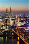 Illuminated Cologne Cathedral, Hohenzollern Railroad Bridge and city skyline at dusk, Cologne, Germany