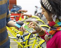 person on phone with credit card - Woman using mobile payment device in bike shop. Stock Photo - Premium Royalty-Freenull, Code: 613-07845155