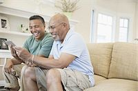 Mature man and father using digital tablet on sofa Stock Photo - Premium Royalty-Freenull, Code: 613-07848349