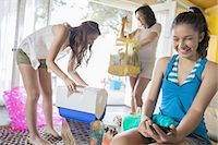 Teen girl using smartphone while sister and mother pack for beach Stock Photo - Premium Royalty-Freenull, Code: 613-07848975
