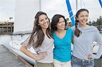 Smiling mother and teenage daughters standing against sailboat Stock Photo - Premium Royalty-Freenull, Code: 613-07849051