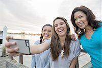 Smiling mother and daughters taking self portrait with smartphone Stock Photo - Premium Royalty-Freenull, Code: 613-07849075