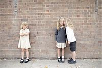 school girl uniforms - Bullying and whispering in school playground Stock Photo - Premium Royalty-Freenull, Code: 613-07849352
