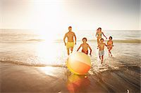 families playing on the beach - Family playing with a beach ball by the sea Stock Photo - Premium Royalty-Freenull, Code: 613-07849410