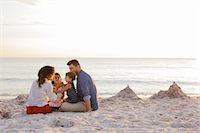 Couple with two girls eating cakes on beach, Tuscany, Italy Stock Photo - Premium Royalty-Freenull, Code: 649-07905280