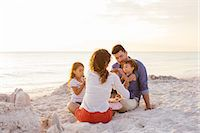 Couple with two girls picnicing with cakes on beach, Tuscany, Italy Stock Photo - Premium Royalty-Freenull, Code: 649-07905281