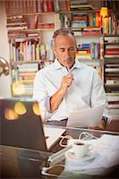 Businessman reading paperwork at home office desk Stock Photo - Premium Royalty-Freenull, Code: 6113-07906169