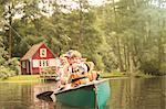 Father and sons fishing from canoe in lake