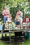 Brothers, father and grandfather wearing life jackets at lake