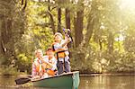 Boy, father and grandfather fishing from canoe on lake