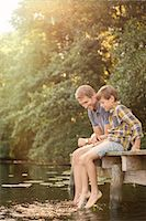 Father and son dangling feet in lake Stock Photo - Premium Royalty-Freenull, Code: 6113-07906374