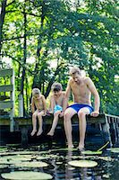Father and sons dangling feet in lake Stock Photo - Premium Royalty-Freenull, Code: 6113-07906383