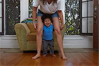 Male toddler taking first steps with mother in sitting room Stock Photo - Premium Royalty-Freenull, Code: 614-07911891