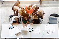 Overhead view of huddled business team meeting at desk in office Stock Photo - Premium Royalty-Freenull, Code: 614-07911918