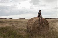 Teenage boy sitting on haystack in field, South Dakota, USA Stock Photo - Premium Royalty-Freenull, Code: 614-07912004