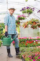 Full-length portrait of smiling man carrying watering can in greenhouse Stock Photo - Premium Royalty-Freenull, Code: 693-07912858
