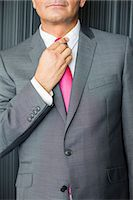 Midsection of mature businessman adjusting necktie Stock Photo - Premium Royalty-Freenull, Code: 693-07913262