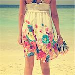 Rear view single girl standing alone at beach, hand holding flower bouquet in vintage toned.