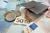 education loan - Euro notes and coins with mini graduation cap Stock Photo - Royalty-Freenull, Code: 400-07915601