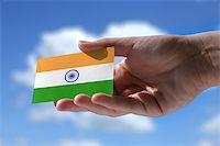 Small Indian flag against sky with cumulus clouds Stock Photo - Royalty-Freenull, Code: 400-07932815