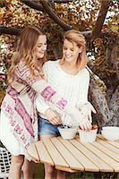 Happy sisters preparing smoothie at outdoors table Stock Photo - Premium Royalty-Freenull, Code: 698-07944523