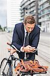 Businessman using smart phone in city while leaning on bicycle