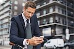 Businessman using smart phone in city