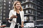 Smiling businesswoman using smart phone in city