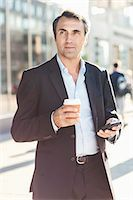 Businessman looking away while holding mobile phone and disposable coffee cup on city street Stock Photo - Premium Royalty-Freenull, Code: 698-07944663