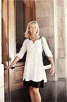 Portrait of happy woman opening door Stock Photo - Premium Royalty-Freenull, Code: 698-07944749