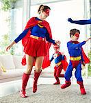 Family of superheroes playing in living room
