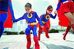 Family of superheroes running on city rooftop