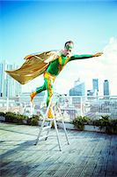 superhero - Superhero posing on stepladder on city rooftop Stock Photo - Premium Royalty-Freenull, Code: 6113-07961684
