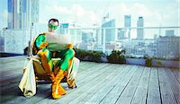 superhero - Superhero reading newspaper on city rooftop Stock Photo - Premium Royalty-Freenull, Code: 6113-07961691