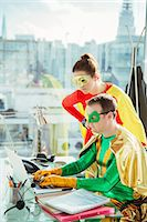 Superheroes working on laptop in office Stock Photo - Premium Royalty-Freenull, Code: 6113-07961695