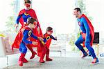 Superhero family chasing each other in living room