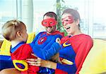 Superhero parents playing with daughter on living room sofa