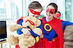 Superhero mother and daughter playing with teddy bear