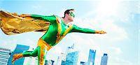 superhero - Superhero flying on city rooftop Stock Photo - Premium Royalty-Freenull, Code: 6113-07961713