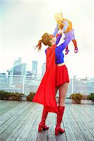 superhero - Superhero mother playing with daughter on city rooftop Stock Photo - Premium Royalty-Freenull, Code: 6113-07961714