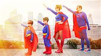 superhero - Superhero family standing with arms outstretched on city rooftop Stock Photo - Premium Royalty-Freenull, Code: 6113-07961716