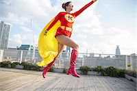 superhero - Superhero jumping on city rooftop Stock Photo - Premium Royalty-Freenull, Code: 6113-07961718