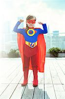 Superhero girl flexing muscles on city rooftop Stock Photo - Premium Royalty-Freenull, Code: 6113-07961721