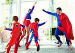 Superhero family playing in living room