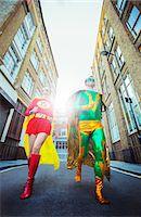 superhero - Low angle view of superhero couple running on city street Stock Photo - Premium Royalty-Freenull, Code: 6113-07961732