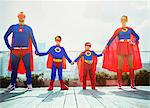 Superhero family holding hands on city rooftop