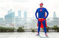 superhero - Superhero standing with hands on hips on city rooftop Stock Photo - Premium Royalty-Freenull, Code: 6113-07961740