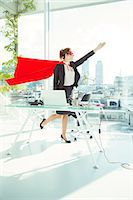 superhero - Businesswoman preparing to fly in cape and mask in office Stock Photo - Premium Royalty-Freenull, Code: 6113-07961746