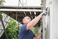 Man renovating wall outside house painting Stock Photo - Premium Royalty-Freenull, Code: 6121-07970029