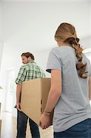 Carrying boxes moving in couple house Stock Photo - Premium Royalty-Freenull, Code: 6121-07970093